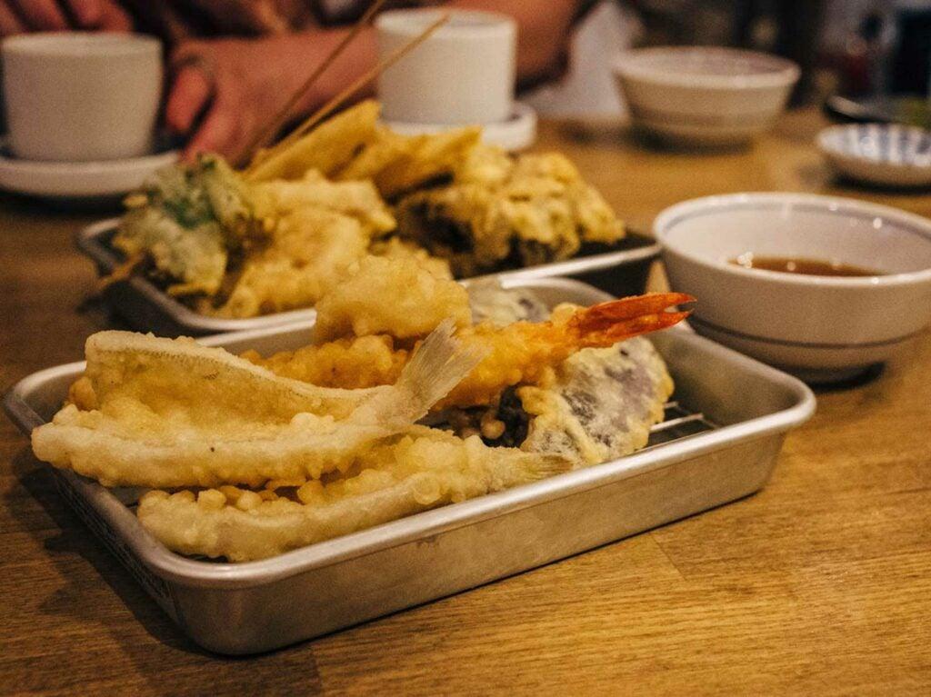 A mixed tempura selection of kisu, prawn, squid, eggplant, okra, lotus root, and maitake mushrooms