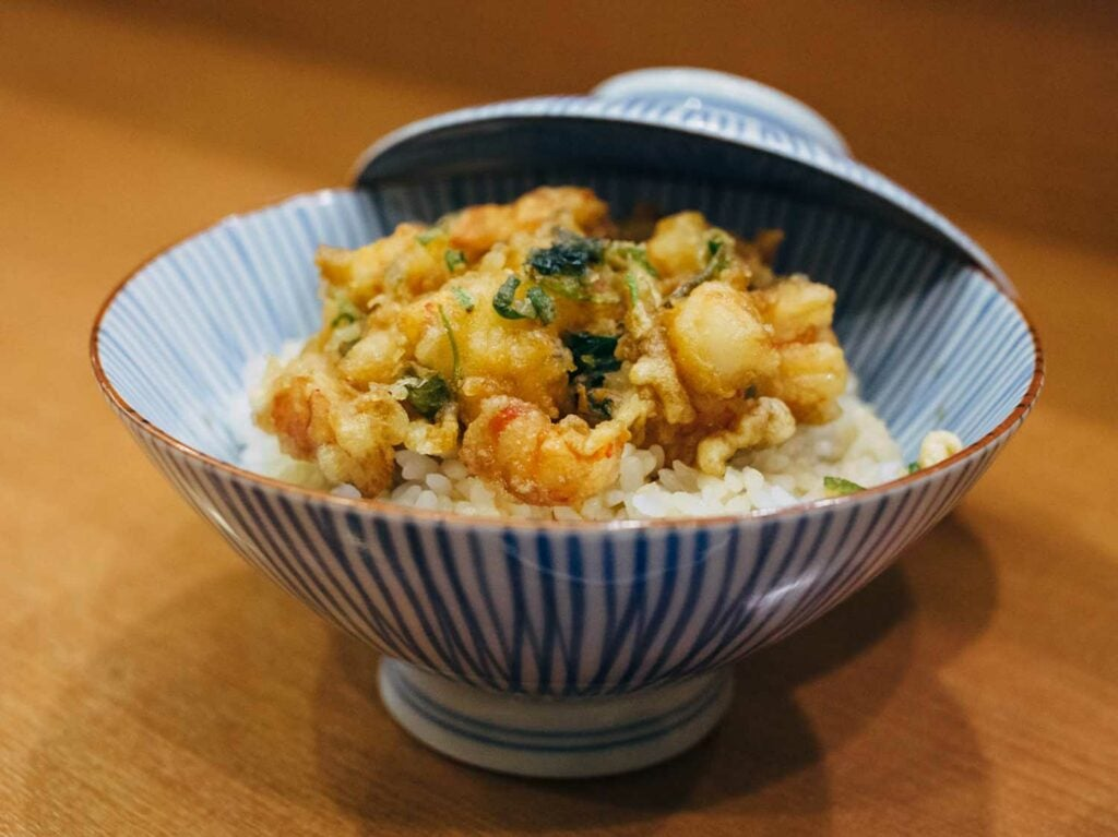 A bowl of rice is crowned with fritter-like prawn and scallop kakiage and doused in hot green tea just before serving.