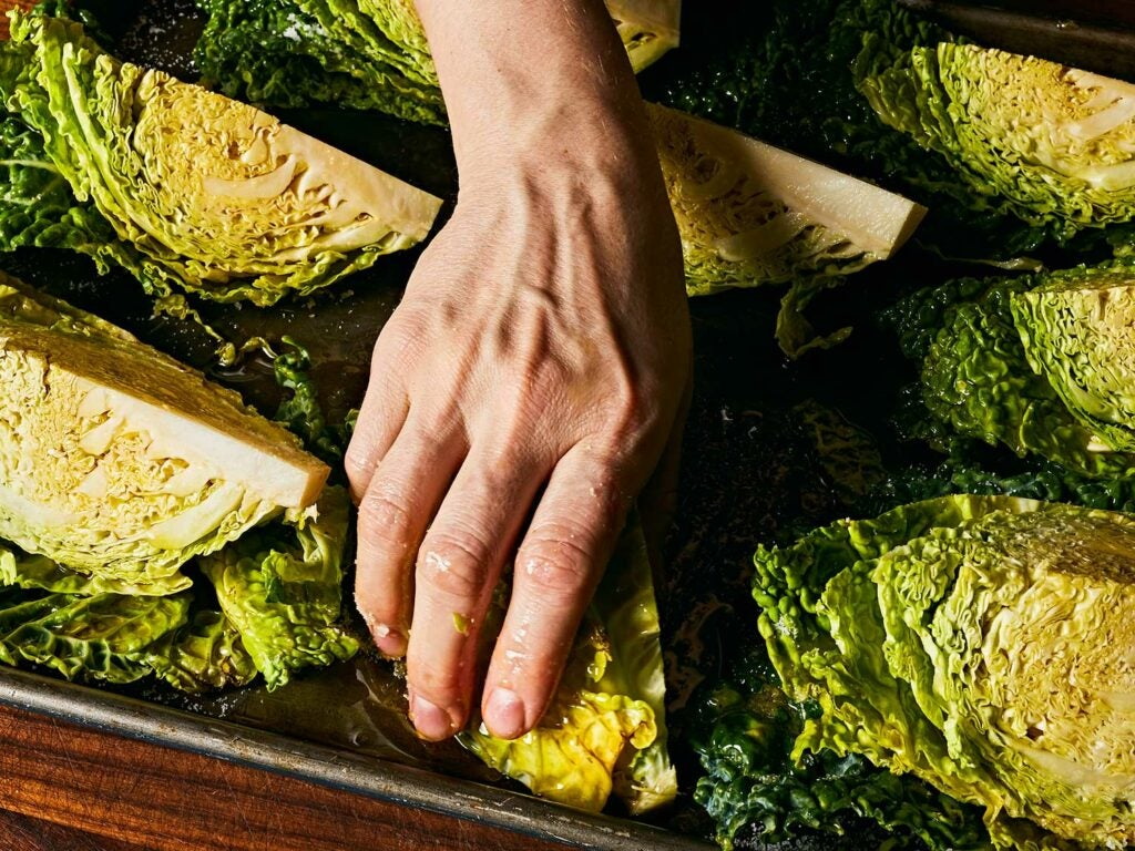 Massaging cabbage with olive oil.