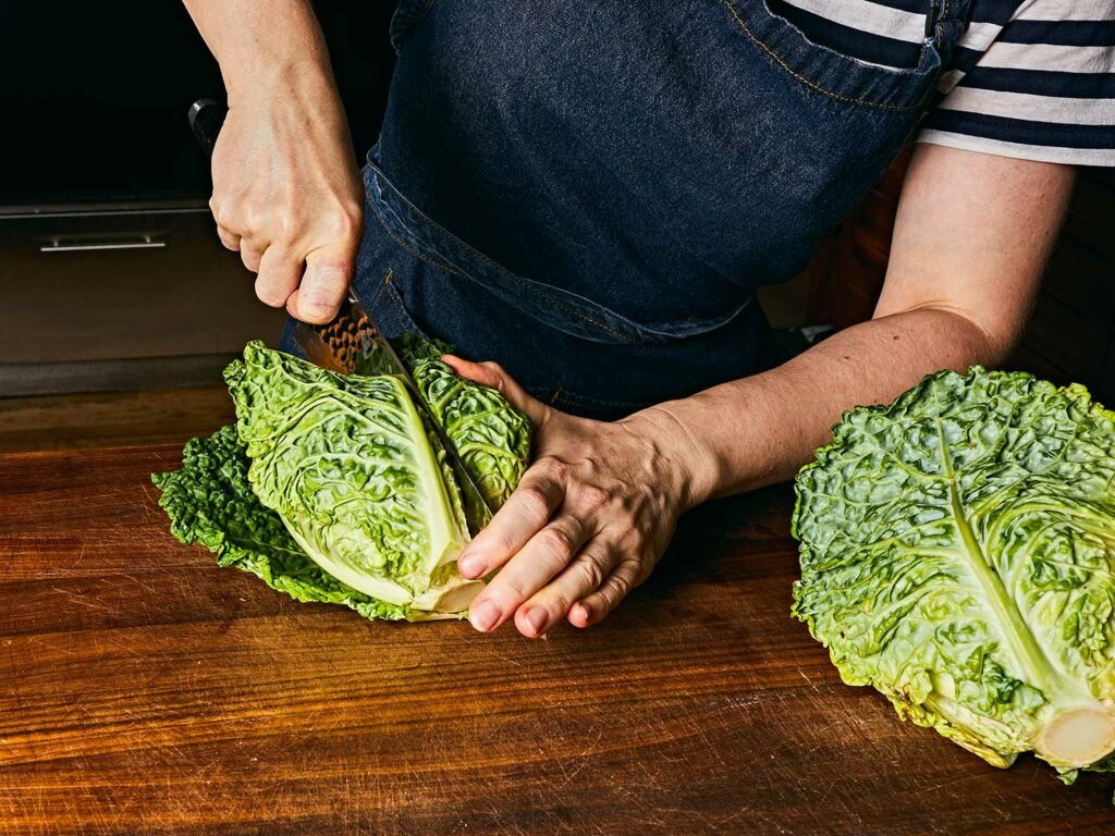 Cutting savoy cabbage into quarters.