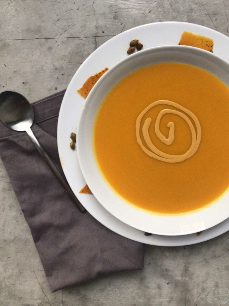 Smoked pumpkin soup spiked with Scotch bonnet chiles and garnished with a swirl of coconut cream.