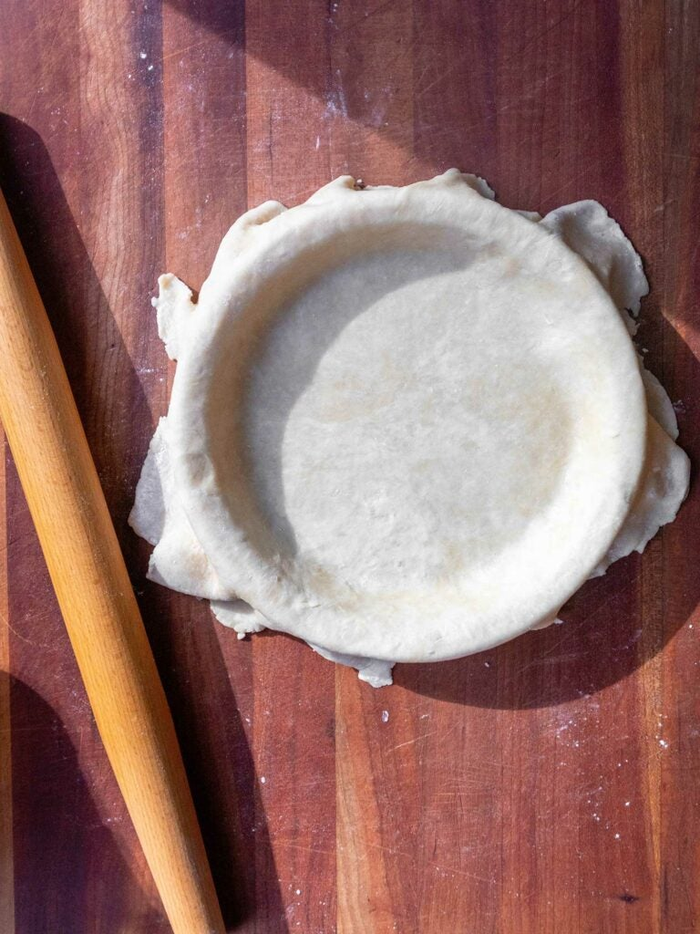 Pie crust in pie plate with rolling pin on countertop.