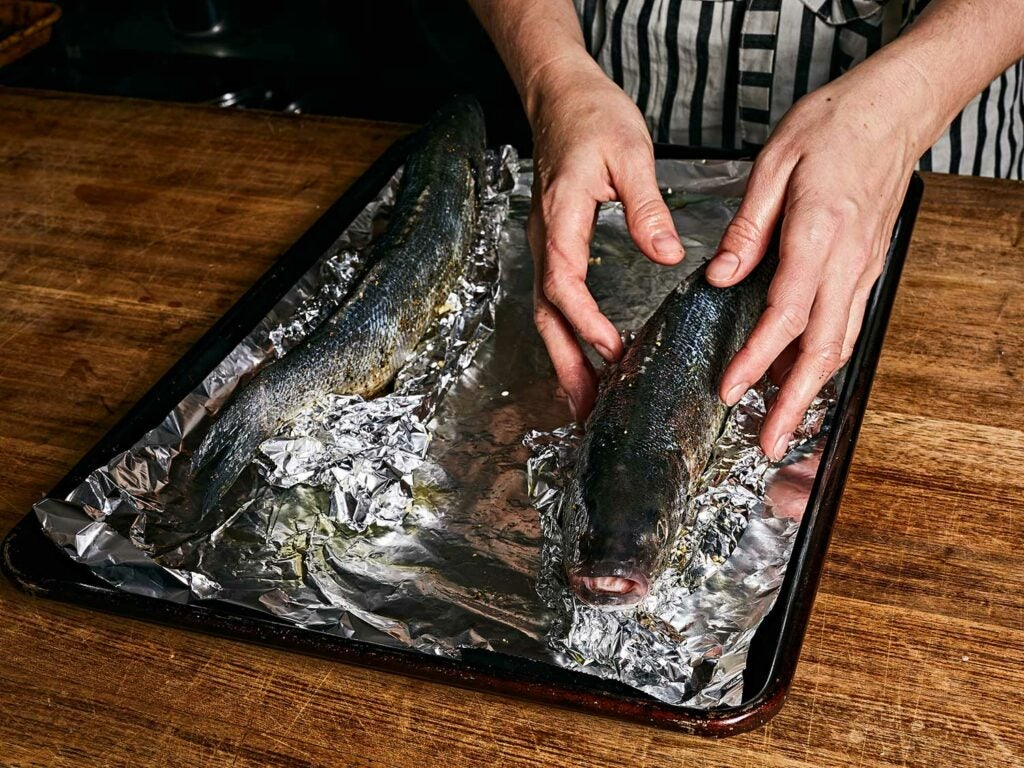 Propping the fish upright and covering in aluminum foil.