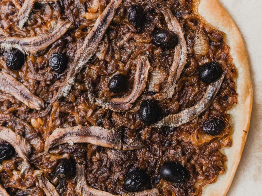 Anchovies can be cooked with the onions, or draped over the top of the tart.