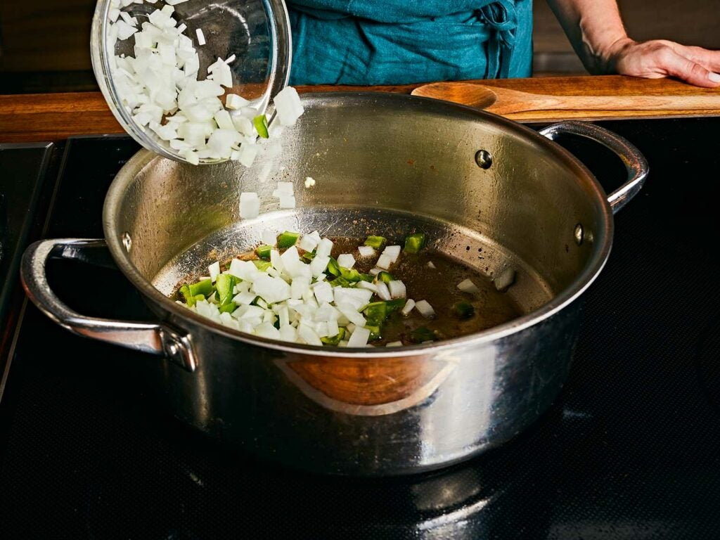 Cooking onion, green bell pepper, garlic, and bay leaves in the chicken fat left in the pot.