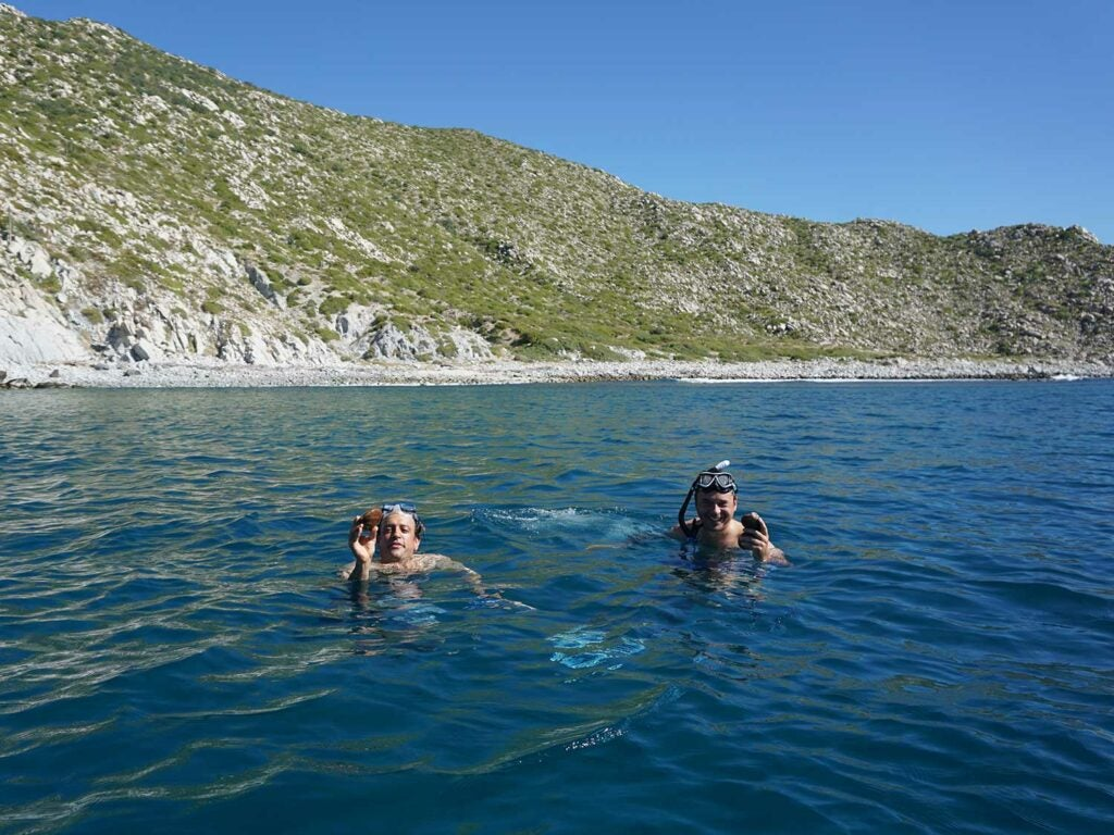 Diving for chocolate clams along East Cape with chef Gomez (right).