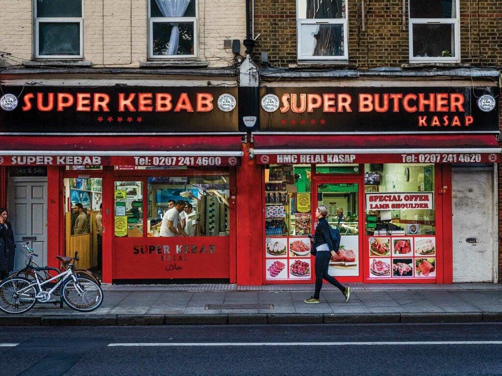 A woman walks by a kebab shop in London.