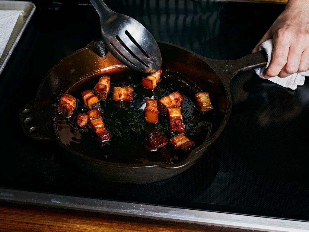 Cooking slab bacon in a hot cast-iron skillet with duck fat or butter until crisp.