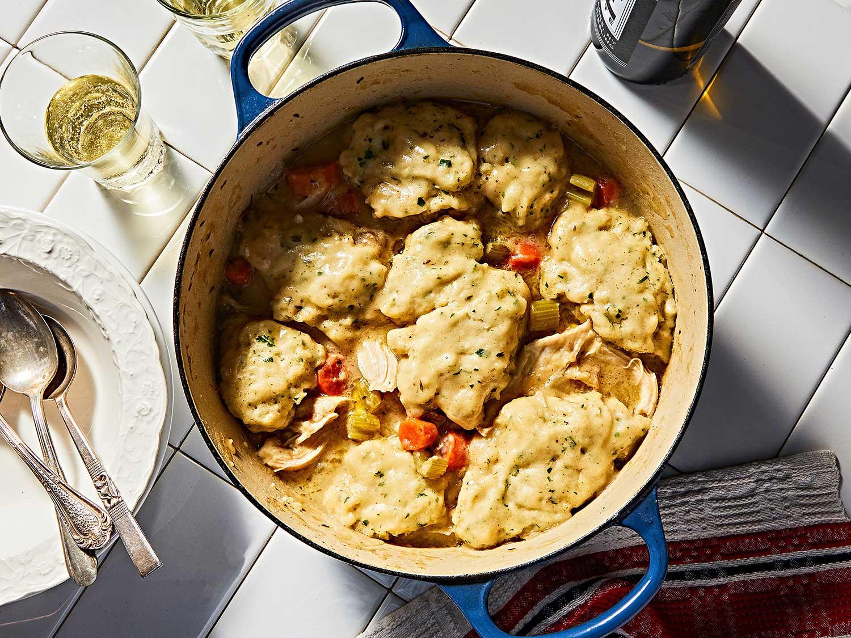 Dumplings cooked on top of chicken in pot.