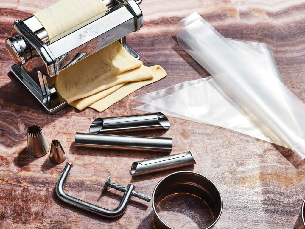 A pasta roller, piping tips, a ring cutter, and cannoli molds with rolled pastry.