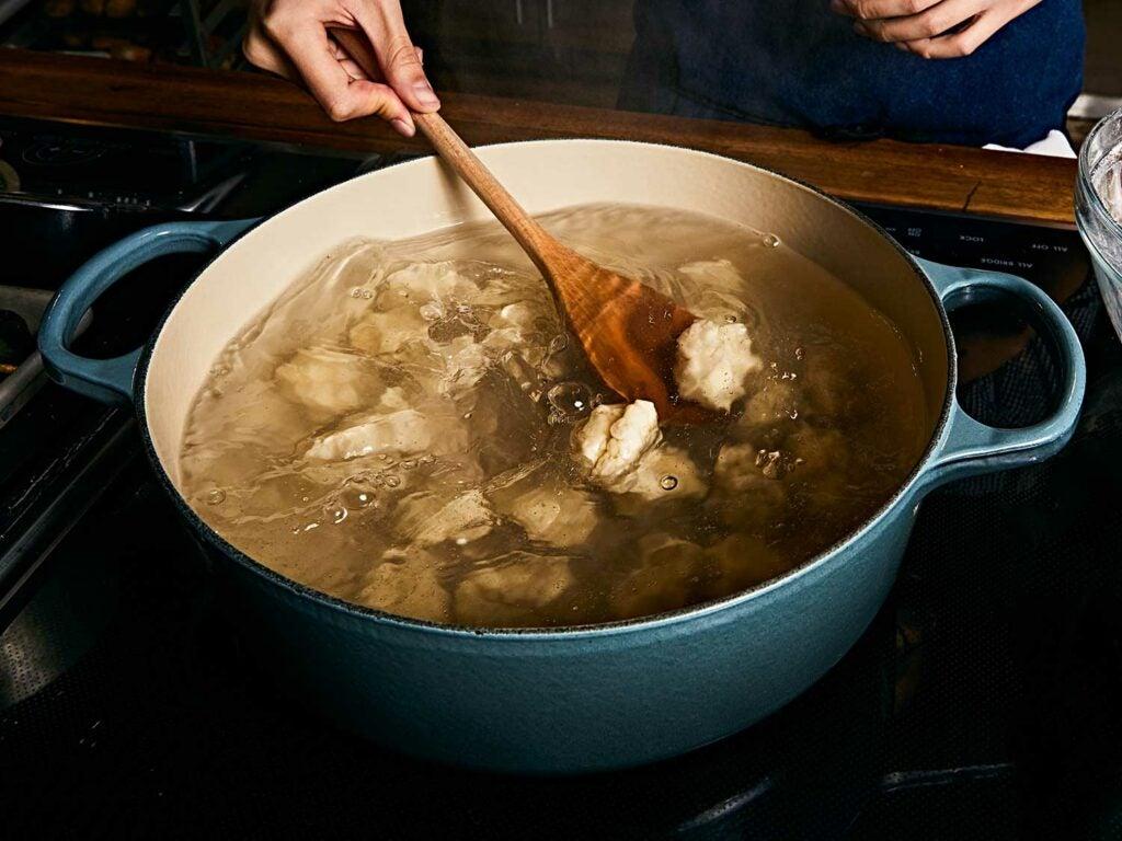 Dumplings boiling in pot.