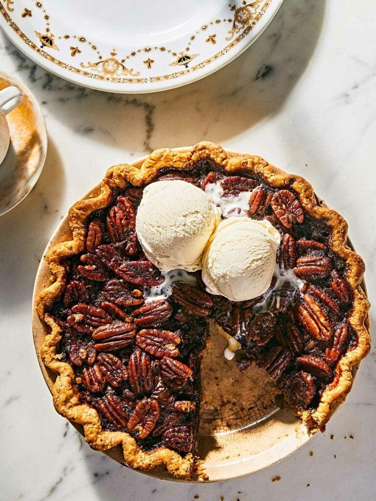Scoops of vanilla ice cream on top of bourbon chocolate pecan pie.