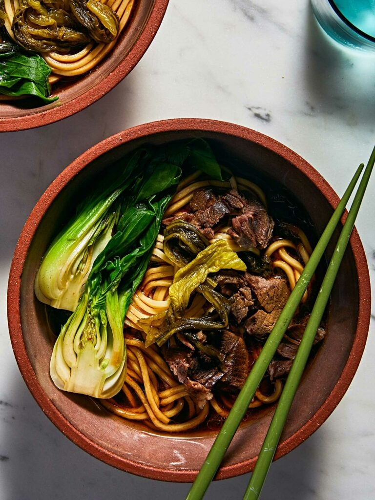 Blanched baby bok choy and pickled Chinese greens in Taiwanese beef noodle soup.