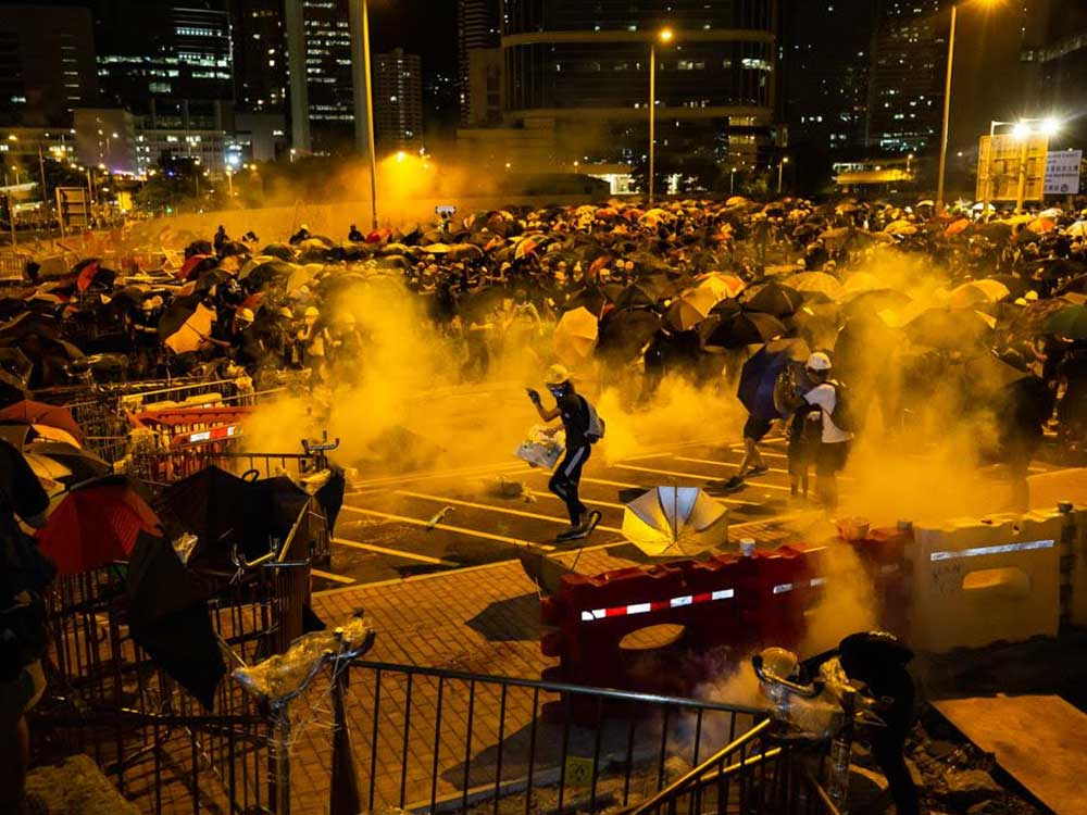 A photo of Hong Kong police firing tear gas into a crowd of protestors, taken this past summer by chef Todd Darling.
