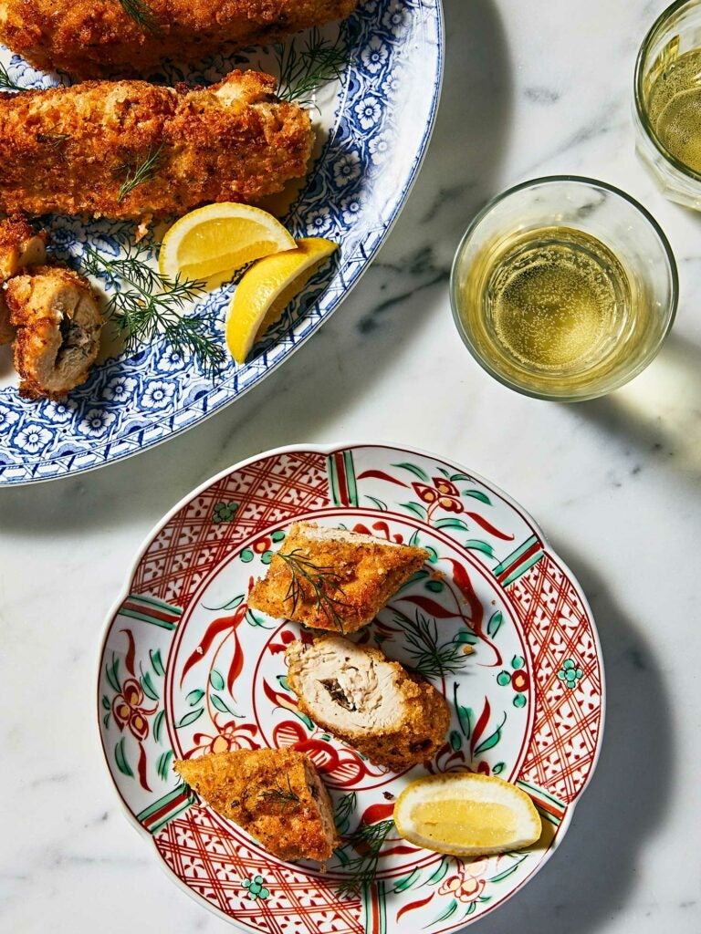 Chicken Kiev with lemon wedges for squeezing and drink.