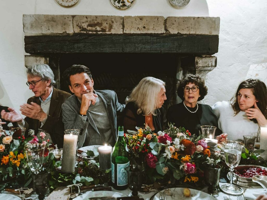 Guests sitting at table at holiday meal.