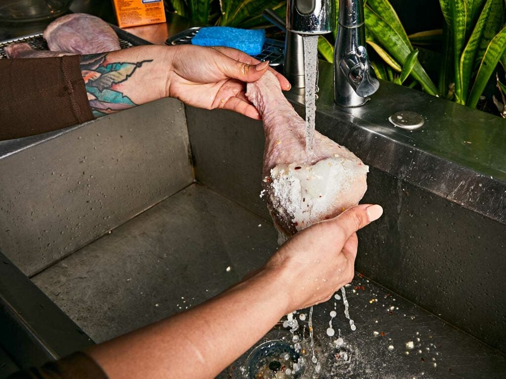 Rinsing turkey leg with cold running water to remove the dry brine.