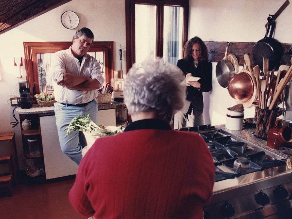 Saveur's first editor-in-chief, Dorothy Kalins (right), and executive editor, Colman Andrews, in the Venice, Italy, kitchen of the late Marcella Hazan, whose back is toward the camera.