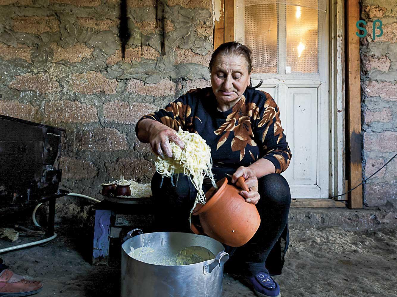 Woman cooking pasta in metal pot.