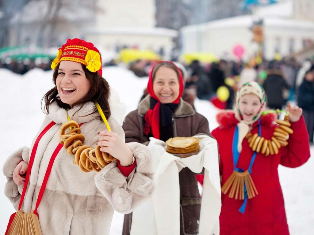 Festival goers celebrate with blinis and necklaces of sushki—an Eastern European sweet bread ring.