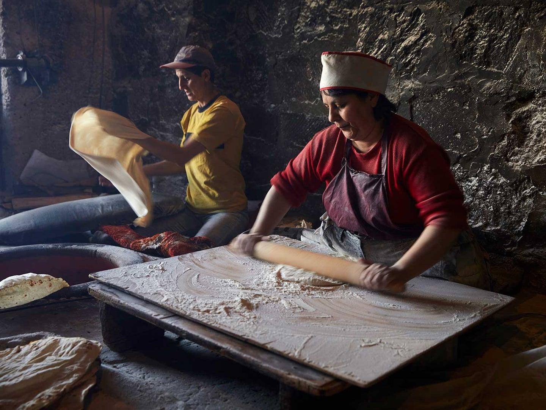 Women roll out lavash dough.