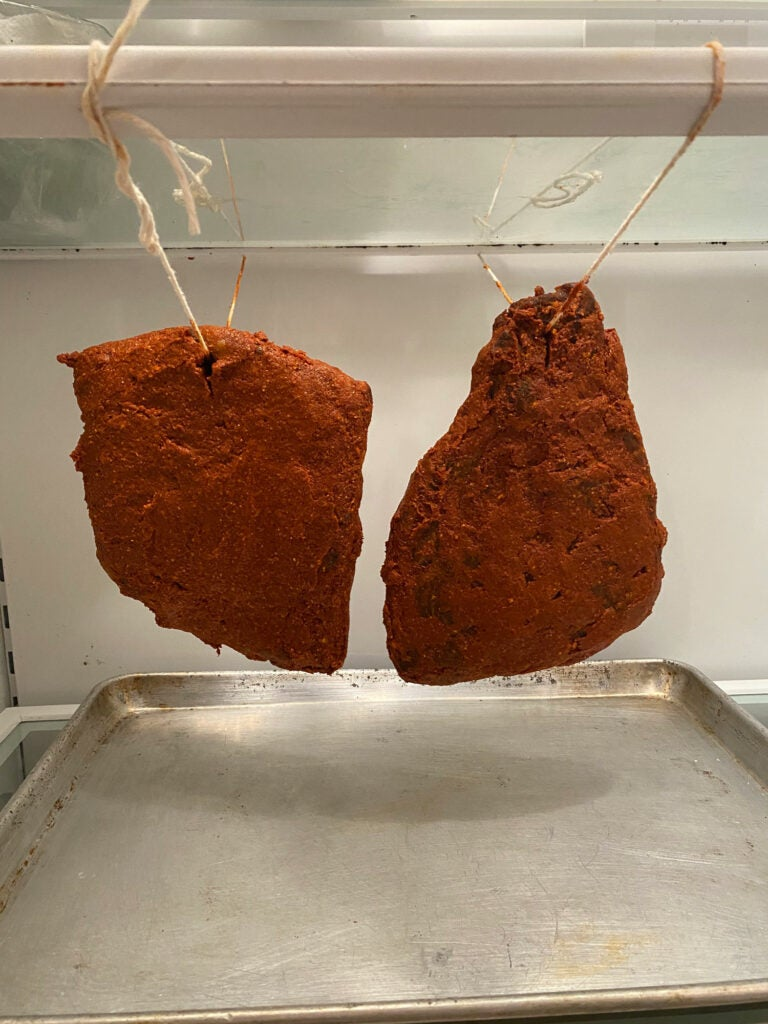 spiced meat hanging in a fridge