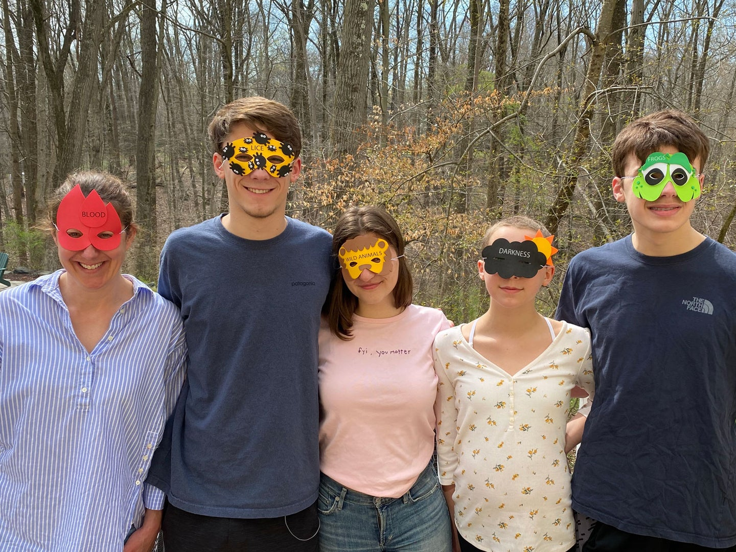"""Author Catherine Tillman Whalen (far left, """"blood""""), her three children (Jack, second from left, """"lice""""; her daughter, second from right, """"darkness""""; her younger son, far right, """"frogs"""") and their """"plus one"""", Ava (center, """"wild animals"""") don masks representing a few of the ten plagues on Egypt."""