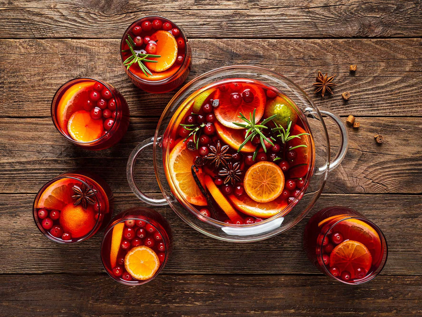 Punch bowl full of orang slices, cranberries, and punch.