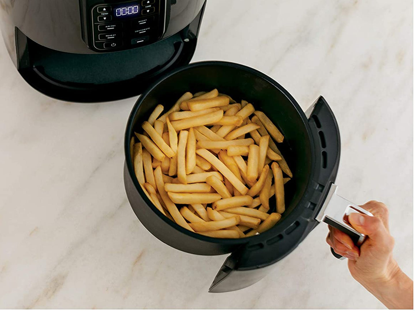 Man cooking french fries in an air fryer