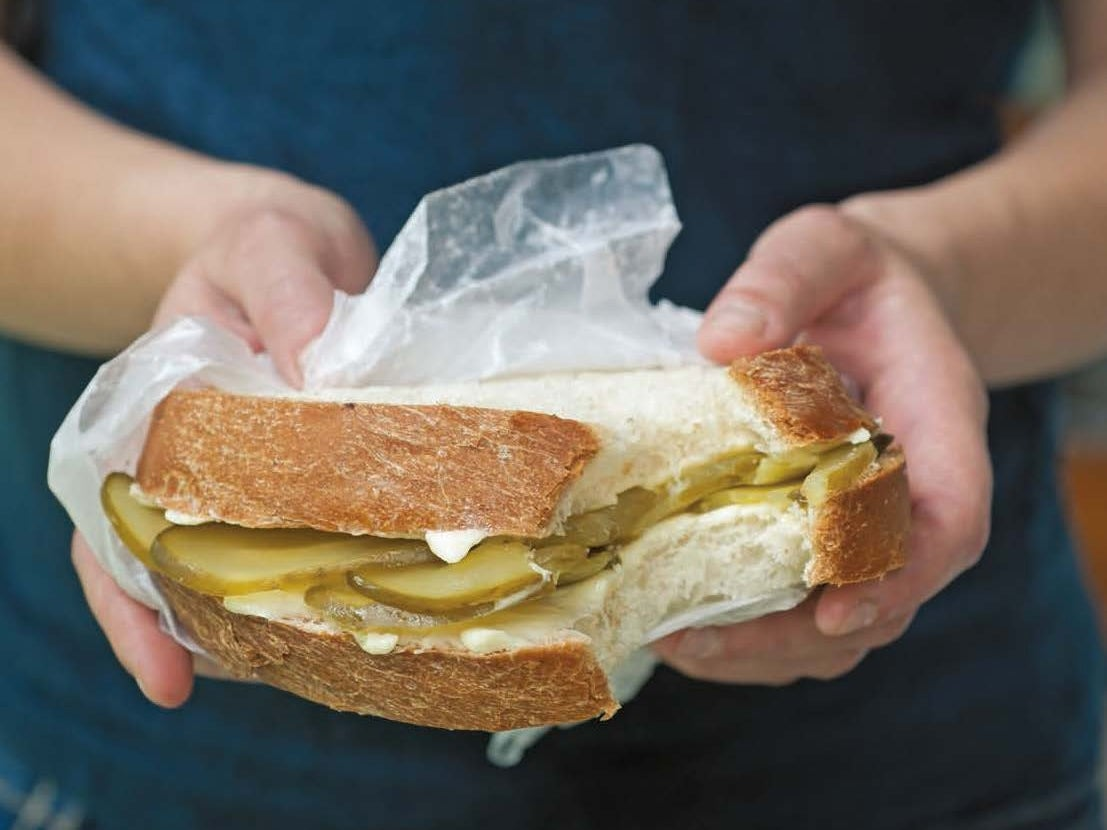 Person holding a bread-and-butter pickle sandwich