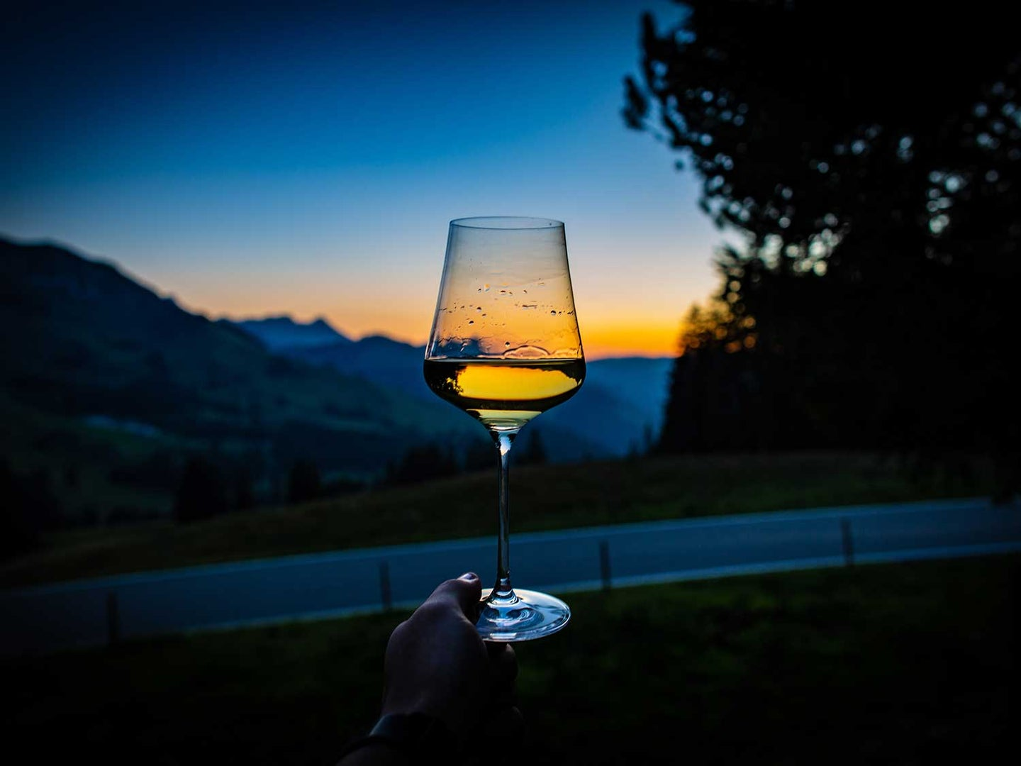 Glass of wine in front of sunset in mountains.
