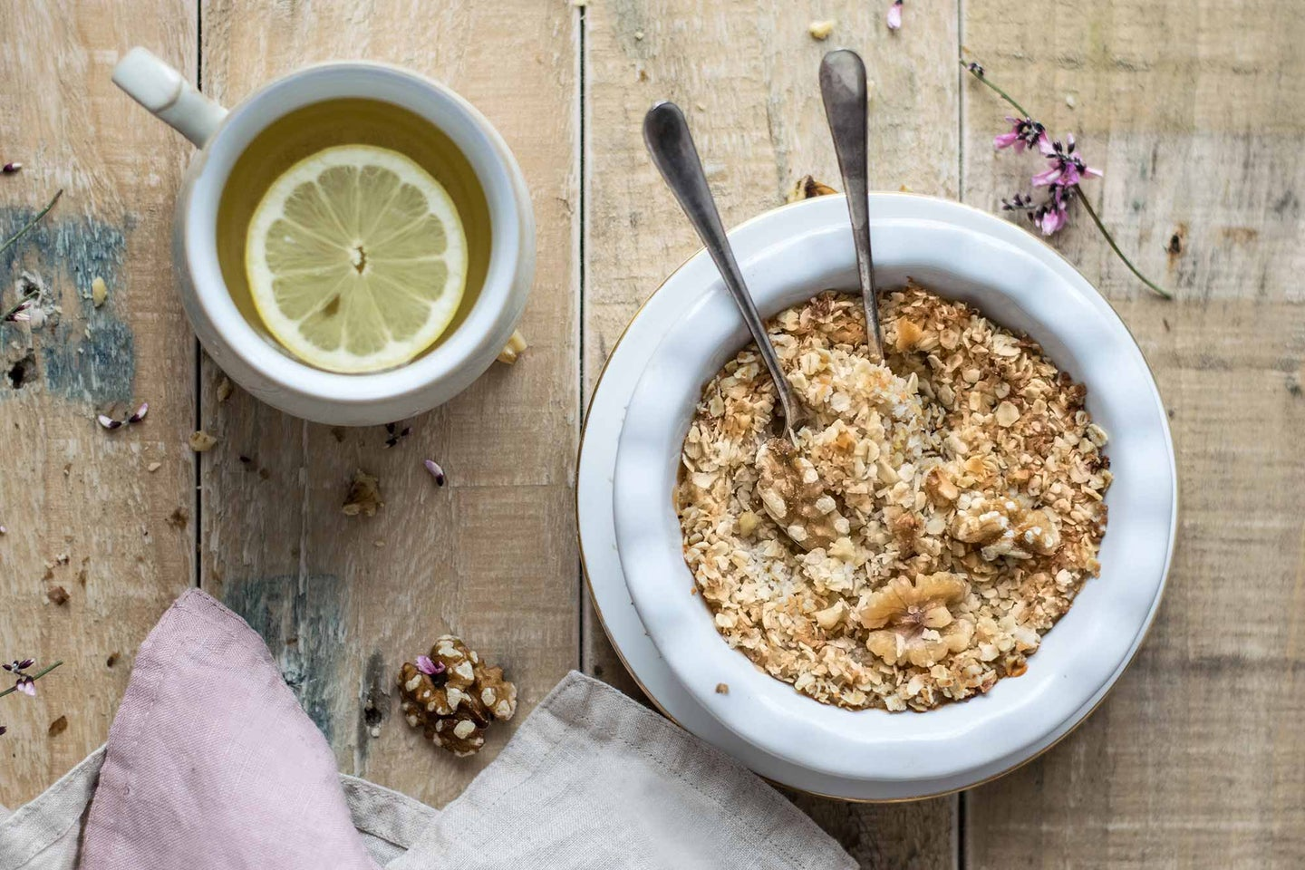 Bowl of oatmeal and cup of tea with lemon.