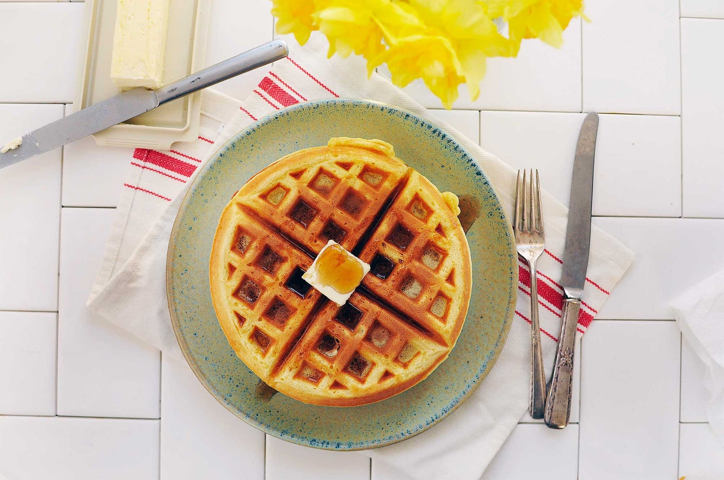 Waffle with dollop of butter and syrup
