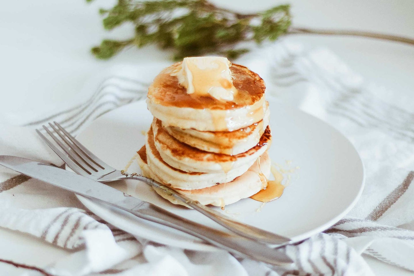 Stack of pancakes with chunk of butter and syrup dripping