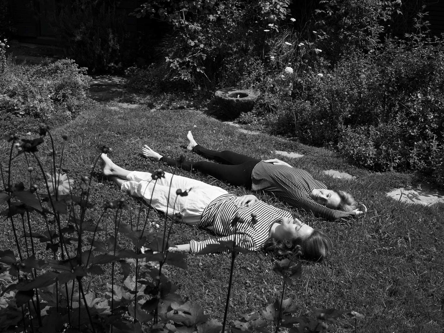 Fanny Singer relaxes in grass with mom Alice Waters at the family home in Berkeley, California.