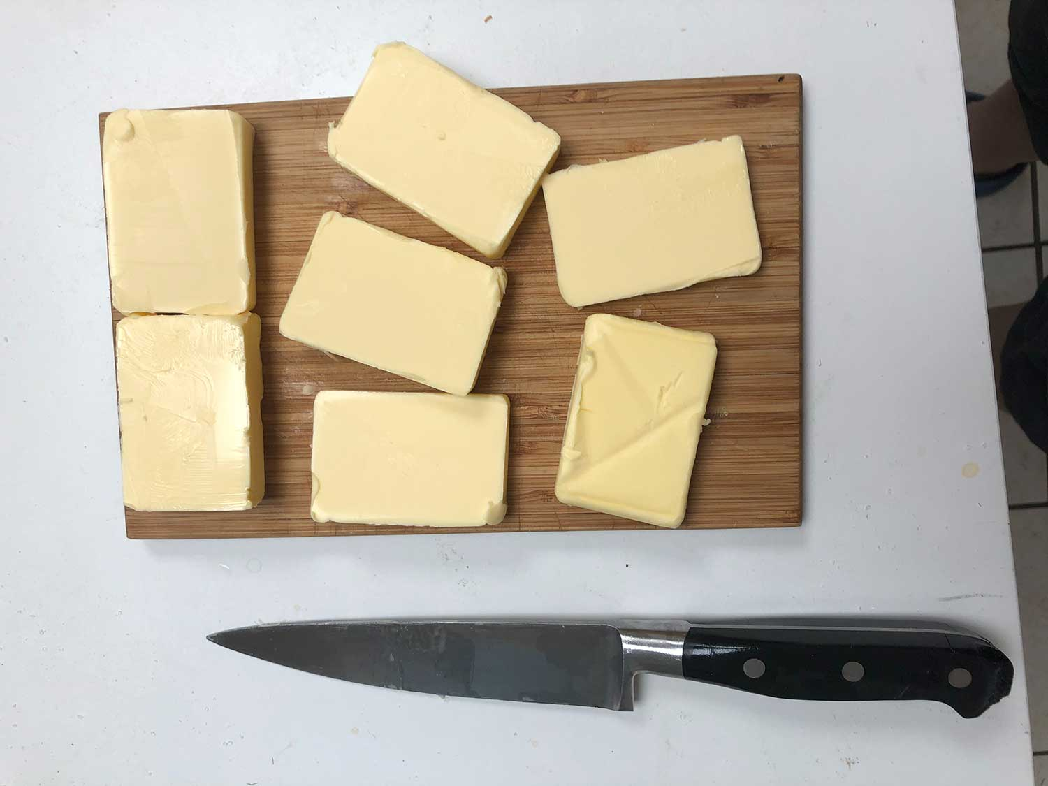 Knife with cheese on cutting board.
