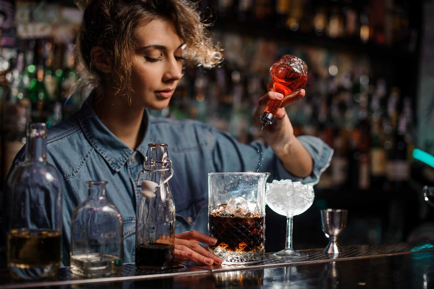 Bartending dashing bitters into a cocktail
