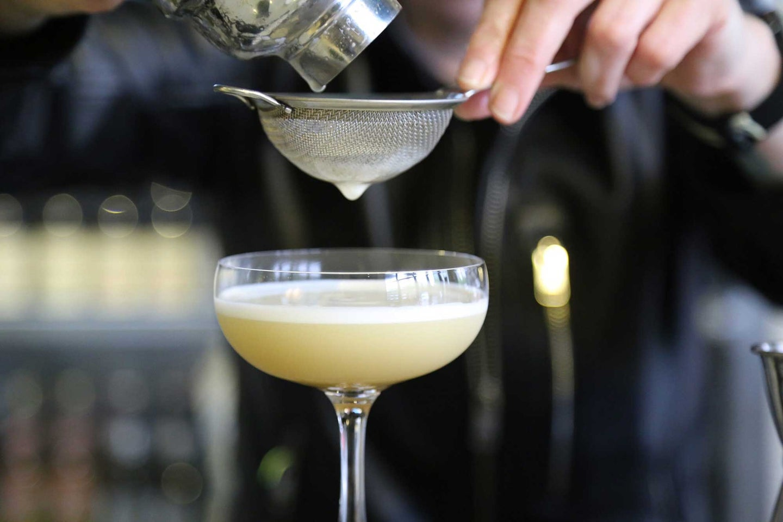Bartender straining a cocktail