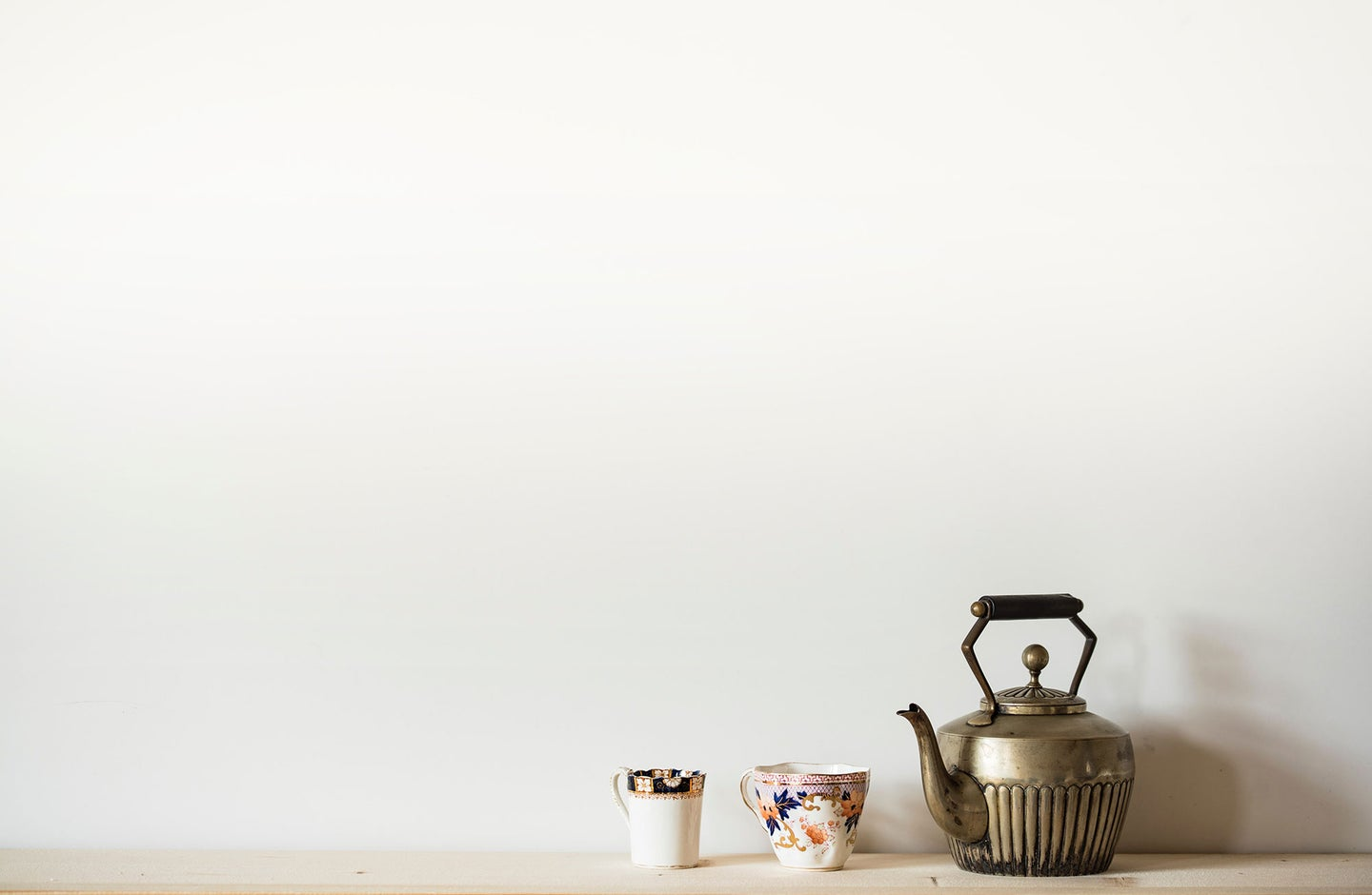 Brass teapot with patterned tea cups.
