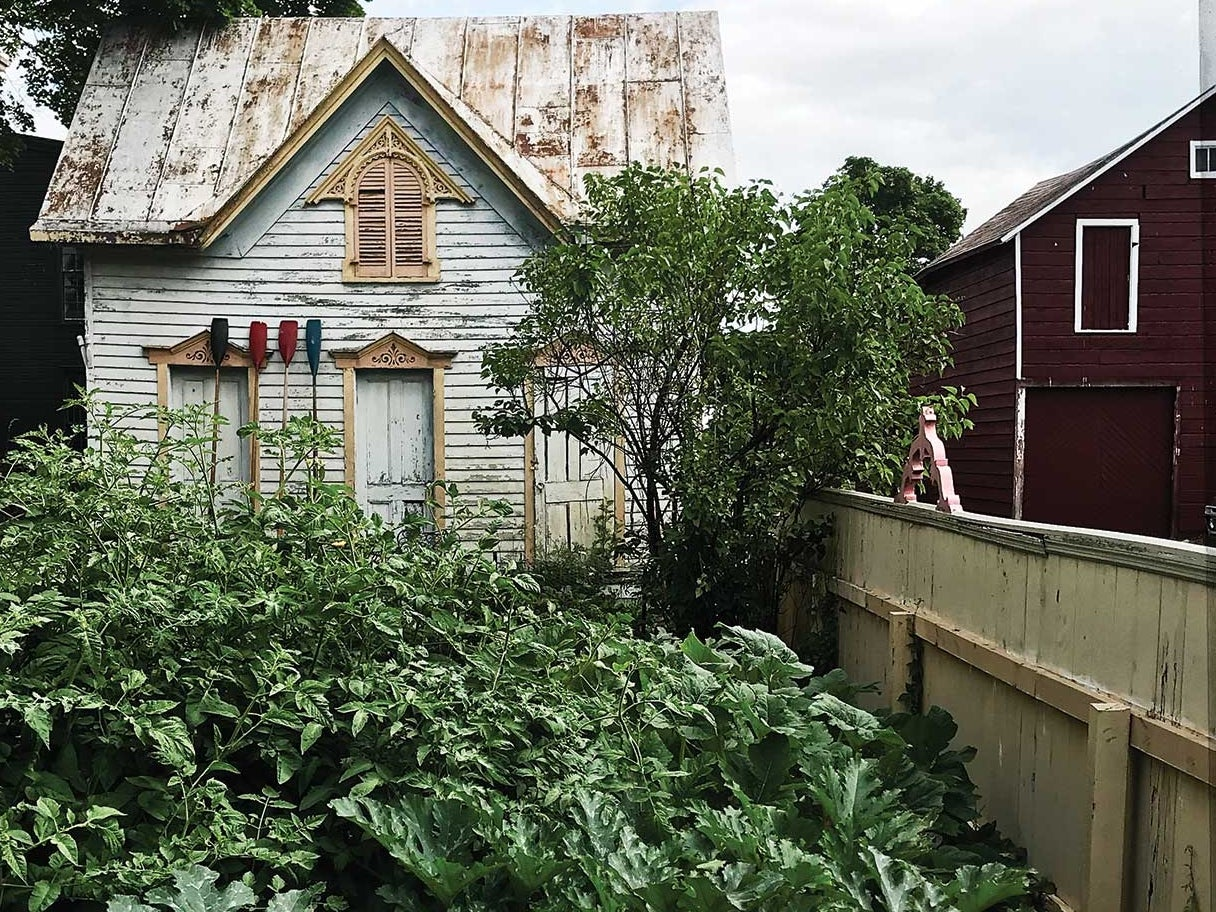 Author Dana Bowen cleared the yard behind her Athens, New York, home to make room for a vegetable garden. The harvest has been plentiful enough to share, so she hangs bags of fresh produce along the fence for neighbors to take.