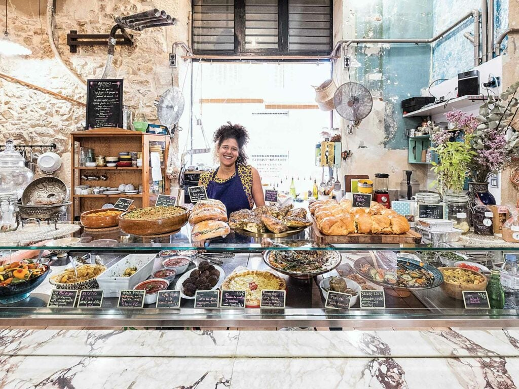 Woman standing behind counter at a bakery
