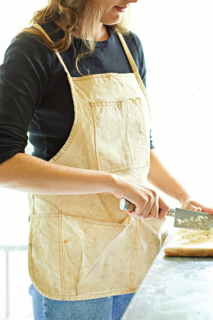 Woman chopping vegetables in a canvas apron