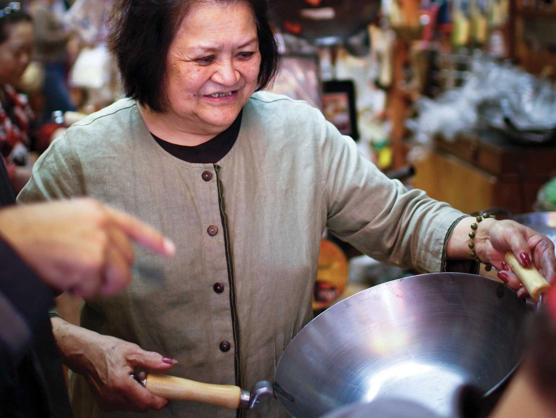 Asian woman holding a wok
