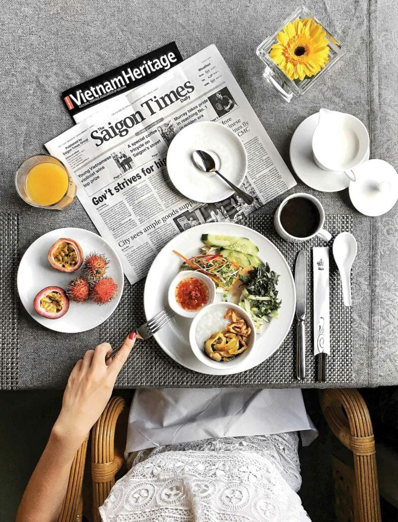 Woman having a meal and reading the Saigon Times