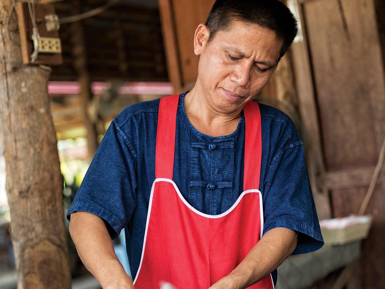 Man wearing red apron and indigo blue shirt