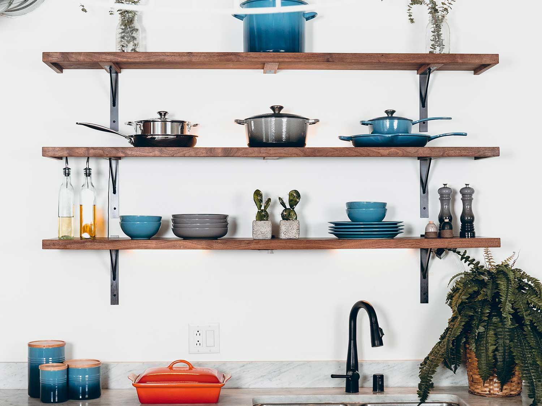 Kitchen utensils hanging about kitchen counter.