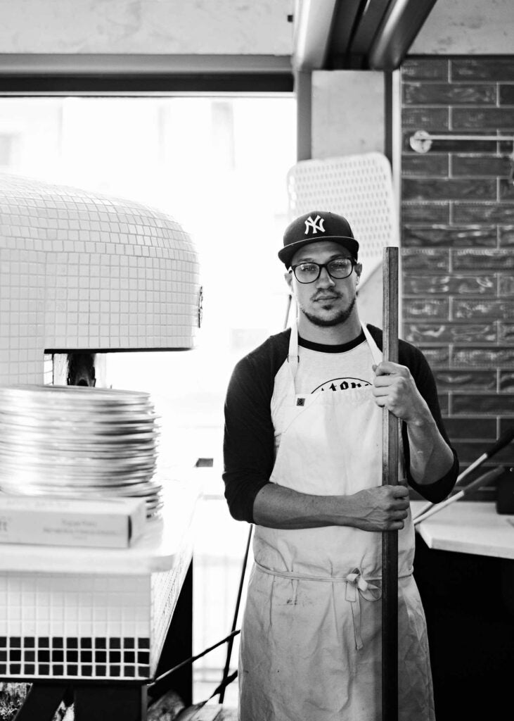 Chef Kyle Jacovino standing beside a pizza oven