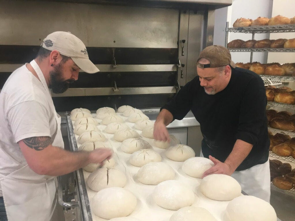 Matt Funiciello (right) scores hand-rolled boules before loading them into the deck oven at Rock Hill Bakehouse.