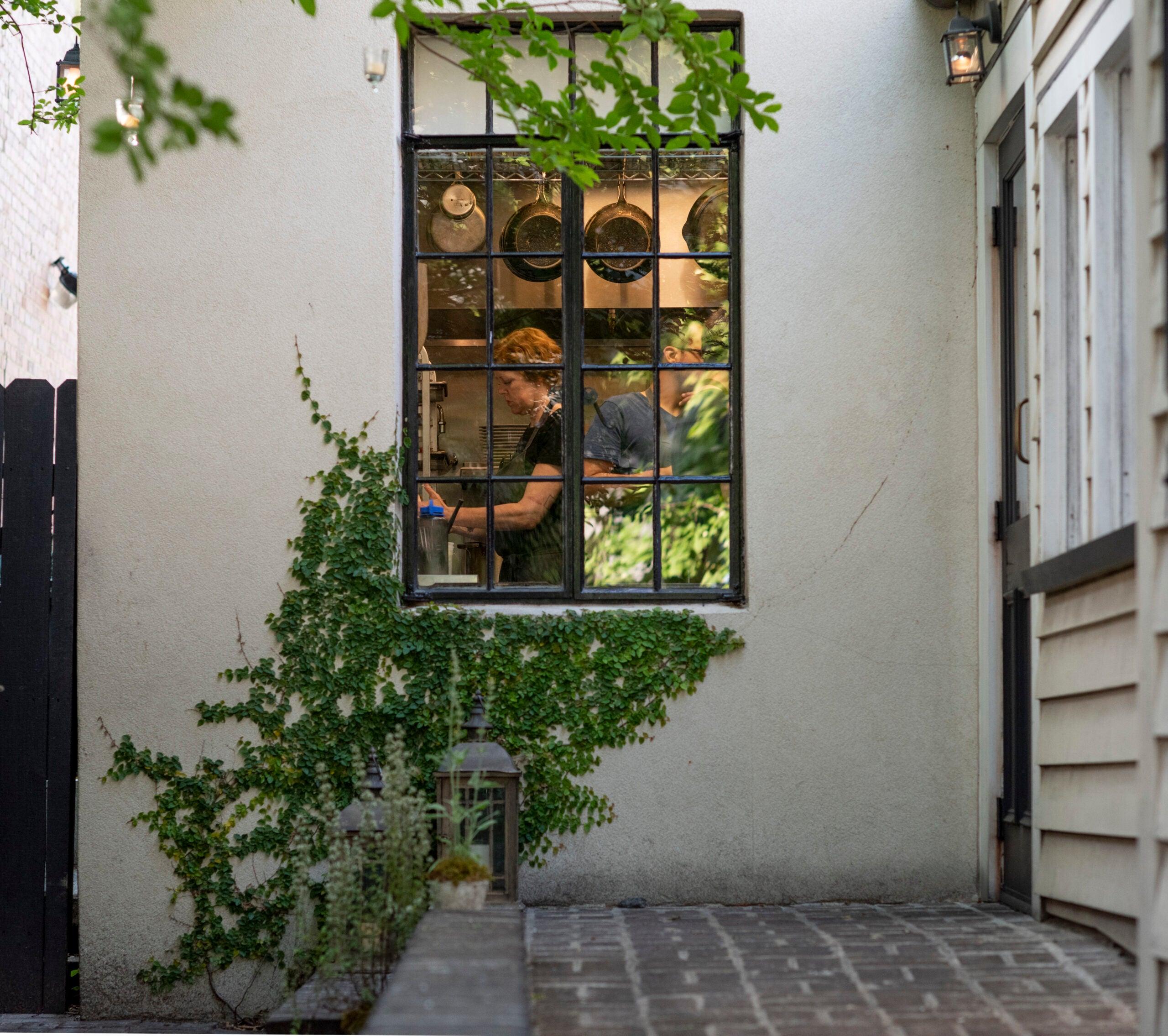 Chef Jill Mathias, seen through the kitchen window at Charleston's Chez Nous.