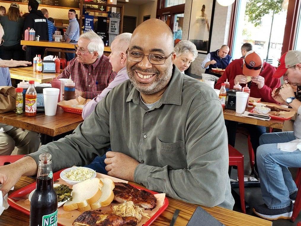 Adrian Miller eating barbecue with tankora seasoning